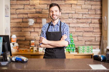 contadores: Apuesto cajero masculino joven que se coloca en la caja y saludar a los clientes con una sonrisa