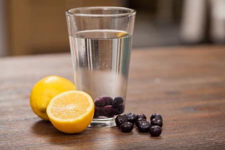 copa de agua: Vaso de agua con limón y arándanos frescos en una mesa de madera en una cocina