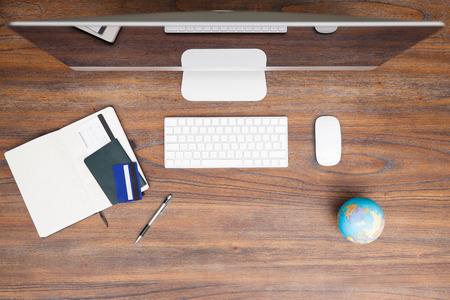Bovenaanzicht van een houten bureau met een computer en een paspoort, reisverslag en een vliegticket klaar om een vlucht te boeken Stockfoto