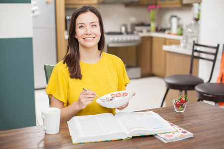 woman eat: Portrait of an attractive young Hispanic brunette eating a healthy breakfast of yogurt with fruit and drinking tea while doing some work at home Stock Photo