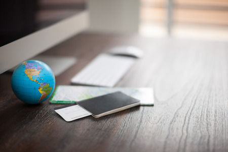 Close-up van het bureau van een wereldreiziger met een paspoort, vliegtickets en een kaart. Foto met ondiepe scherptediepte