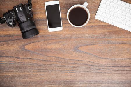 Płaskie biurko biurka fotograficznego z aparatem cyfrowym, smartfonem i kawą z dużą ilością miejsca na kopię