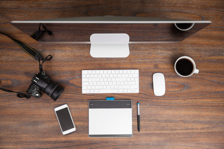 work table: Flat lay view of a computer with a pen tablet and a dslr camera on a wooden desk in a photographer studio