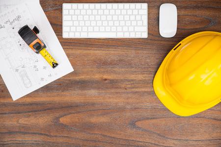 cinta metrica: Opinión de alto ángulo del espacio de trabajo de un contratista con un casco, algunos planes de construcción y una cinta métrica