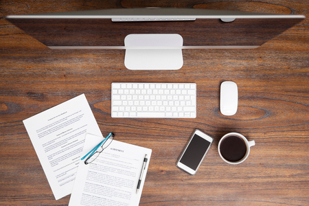 table top: High angle view of a computer, some legal documents and a smartphone in a lawyers workspace Stock Photo