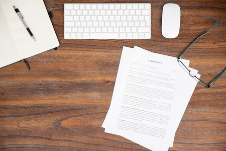 Flat lay of a lawyer's wooden desk with a computer, a notepad, a contract and some glasses