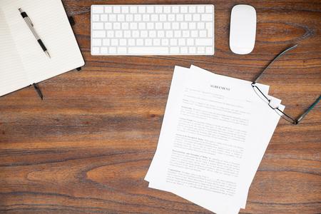 Płaskie leżenie prawnego drewnianego biurka z komputerem, notatnik, kontrakt i okulary Zdjęcie Seryjne