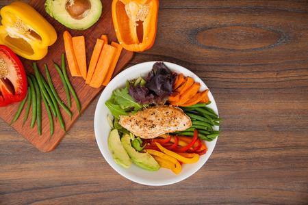 Piatto piatto di un piatto con pollo seduto su un letto di verdure e alcuni dei suoi ingredienti sul lato con un sacco di spazio copia