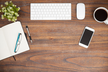 porre piatto di tastiera di un computer, un blocco note, un caffè e uno smartphone in una scrivania in legno