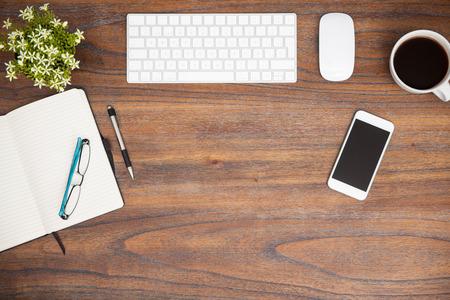 piso: Plano de la puesta de un teclado de computadora, un bloc de notas, un poco de café y un teléfono inteligente en un escritorio de madera