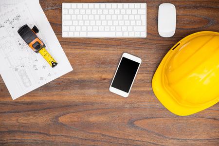 cinta metrica: en plano de área de trabajo de un arquitecto con un ordenador, un casco, algunos planes de construcción y un teléfono inteligente