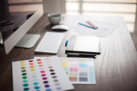 Komputer, pióra, próbki kolorów i szkice na przestrzeni roboczej projektanta z bardzo płytkiej głębi ostrości