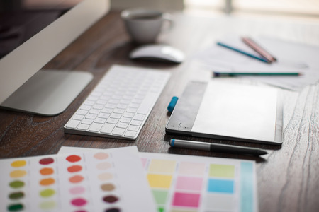 A falta de profundidade de campo do espaço de trabalho de um designer gráfico com uma caneta eletrônica, um computador e algumas amostras de cores