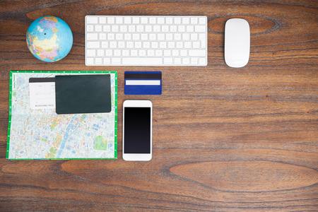 Bovenaanzicht van een bureau van een reiziger met een toetsenbord van de computer, een wereldbol, paspoort, vliegtuig tickes, een kaart, een creditcard en een smartphone