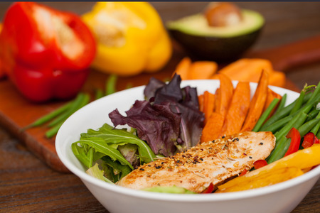 produces: Cooked chicken with spices served on a bowl of lettuce, sweet potato, green beans, avocado and pepper