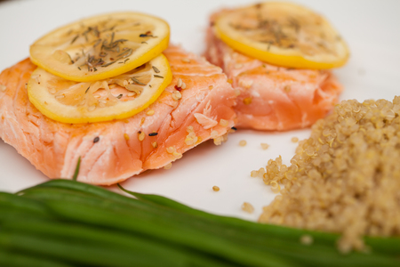 salmons: Macro view of a healthy dinner with salmon, lemon and some herbs next to some quinoa and green beans