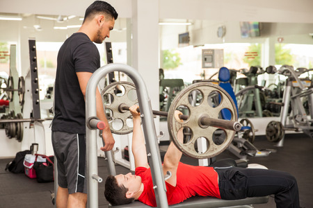 Profile View Of A Personal Trainer Spotting A Young Man While.. Stock  Photo, Picture And Royalty Free Image. Image 53101556.