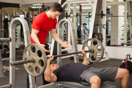 Strong young man spotting another guy while he lifts a barbell at a gym Stock Photo