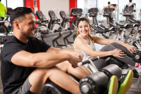 adentro y afuera: Retrato de una morena muy reír y divertirse con su novio mientras hace ejercicio juntos en un gimnasio