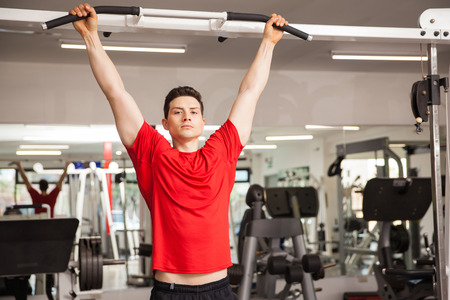 Portrait of an athletic Hispanic young man doing some pullups at the gym and making eye contact