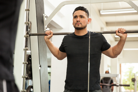 Portrait of a young Hispanic man ready to do some squats on a machine at the gym Foto de archivo