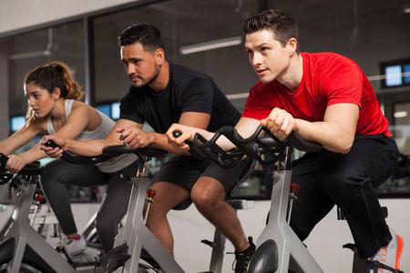 Grupo de tres amigos haciendo algo de cardio en una bicicleta en un gimnasio y concentración en su entrenamiento