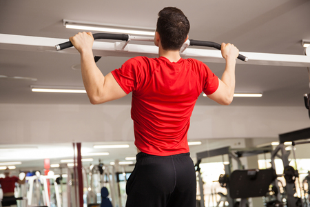 pullups: Rear view of a strong young man doing pullups at the gym