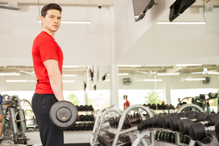 eye contact: Portrait of an attractive young man lifting weights in front of a mirror in a gym and making eye contact Stock Photo