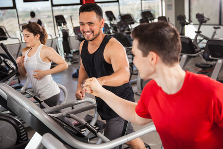 gym workout: Happy young men bumping their fists while doing some jogging on a treadmill at the gym