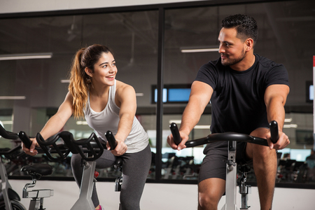 Hermosa mujer hispana joven que liga y hablando con un chico, mientras que ambos hacen algunos de spinning en un gimnasio Foto de archivo
