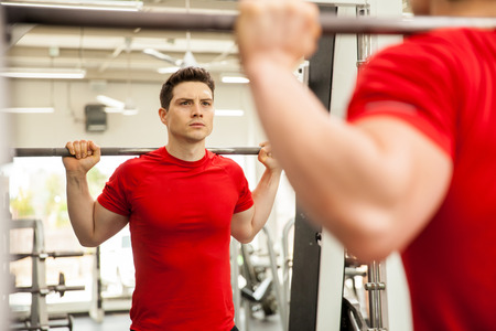 young guy: Portrait of a good looking young man doing some squats on a smith machine