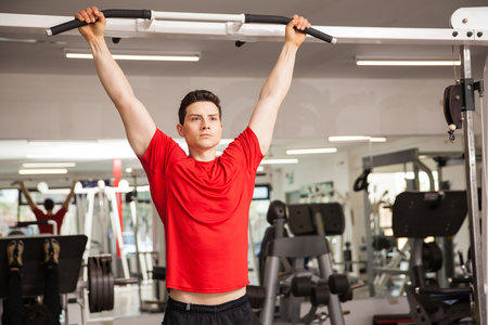 Good looking athletic man concentrating for his pull up workout at the gym