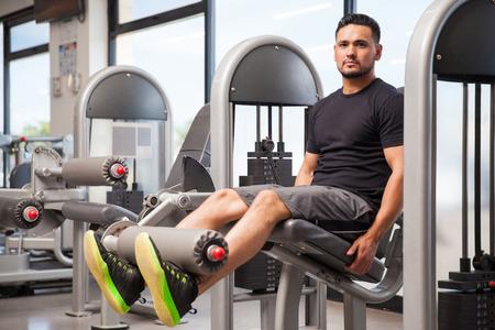 hombres trabajando: Retrato de un hombre joven y guapo haciendo algunos ejercicios para las piernas en el gimnasio