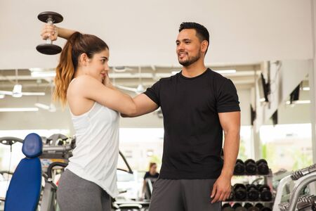 hispanic woman: Hispanic personal trainer helping a young woman with her posture while lifting some weights at the gym Stock Photo