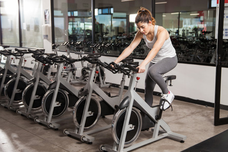 Full length view of a young brunette in sporty outfit doing spinning by herself in an empty gym