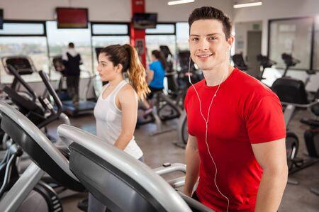 la escucha activa: Retrato de un individuo hermoso escuchar música mientras se hace algo de cardio en una cinta de correr en un gimnasio