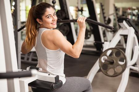 Hispano joven mujer hermosa que se resuelve en una máquina de tirar hacia abajo en el gimnasio