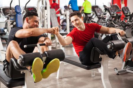 Twee atletische jonge man stoten hun vuisten als een teken van vriendschap en uit te werken samen bij een sportschool