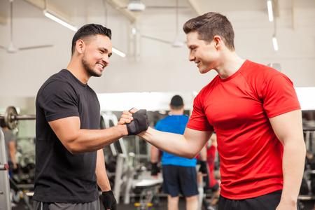 apreton de mano: Dos hombres jóvenes reunidos en el gimnasio y entre sí dando un apretón de manos Foto de archivo