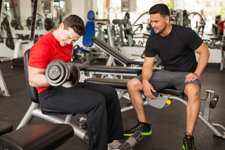 encouraging: Young man spotting and encouraging his male friend while he lifts weights at the gym Stock Photo