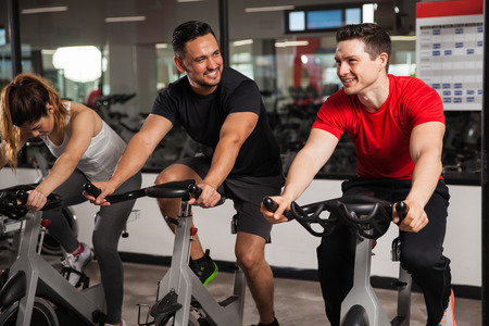 Portrait of a couple of young men talking and laughing while doing some spinning at a gym Archivio Fotografico