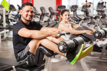 Portrait of a young Hispanic man and his girlfriend doing some crunches and exercising together in a gym