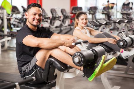 Retrato de un joven hispano y su novia haciendo algunos abdominales y el ejercicio juntos en un gimnasio