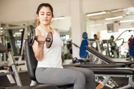 Pretty young brunette doing bicep curls on a bench at the gym