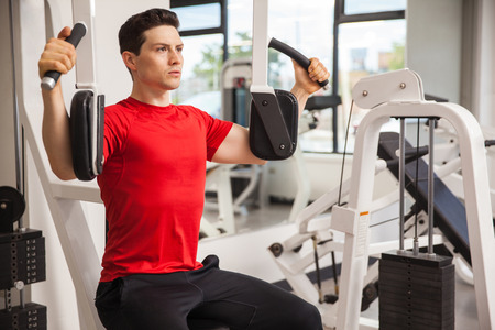 man working out: Portrait of a good looking athletic man working out on a machine at the gym
