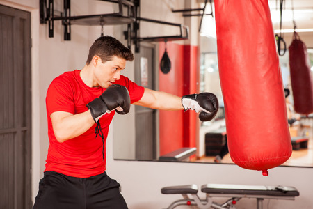 punching bag: Profile view of a good looking young Hispanic man practicing box on a punching bag at the gym