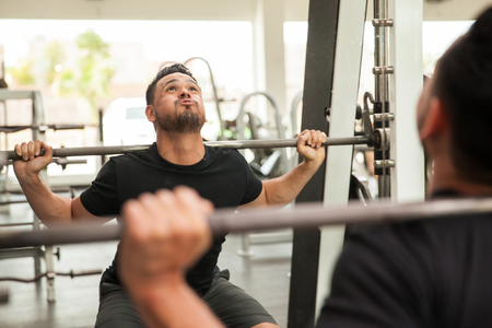 effort: Strong man using a squat machine for his workout at the gym