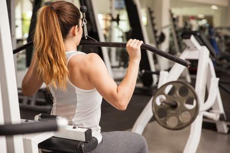 Achteraanzicht van een sterke en atletische vrouw die uitoefent op een lat pulldown machine