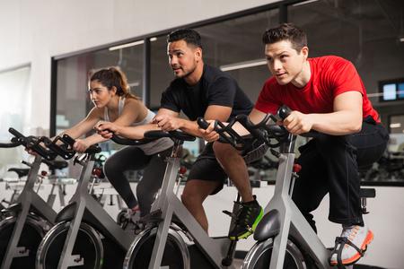 Trois jeunes gens qui font un peu de cardio et d'agir tous concentrés au cours de leur classe de spinning