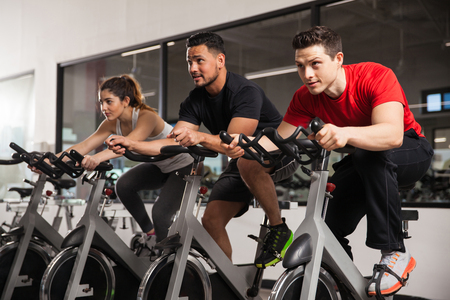 Three young people doing some cardio and acting all focused during their spinning class